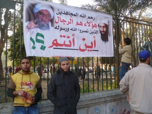 Around 5pm, the police relented and allowed the protestors to advance and demonstrate in front of the embassy, though the police presence guarded it and otherwise surrounded them. Graffiti and other banners were hung in the area, this one across the street on the wall of the Giza Zoo. Pictured are Osama bin Laden and Mohamed's brother Ayman. The sign reads: God have mercy on the jihadists. They are the men who gave victory to God and his prophet. Where are you?!