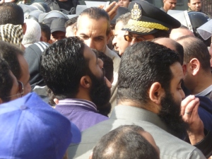 Next to the man in the police cap is Ezzat al-Salamony. He is a leader with the Islamic Group, not the Salafi-Jihadis, and worked to restrain the crowd. He later gave a rousing speech against the French, though, calling for jihad in the lands of the infidels.