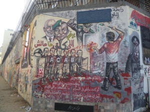 And the walls were updated with the pictures of the latest martyrs and targets of political rejection. Here, the Muslim Brotherhood's General Guide hovers behind a split image of Mubarak and former army General Tantawi.