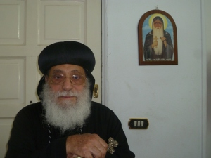 Bishop Antonious Marcos, missionary bishop for Africa. Behind him is a picture of the Coptic saint know as St. Moses the black.
