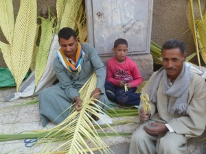 This is a good photo to close with, Coptic street vendors making palm leaves outside a church in Asyut. The little cross the man on the right is holding sold for $1.