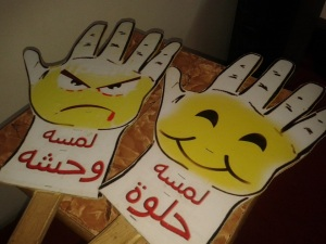 Props used in the children's awareness campaign. The Arabic reads: Bad Touch (L), Good Touch (R)