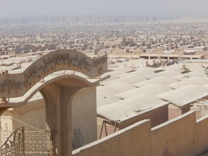 The sign reads: Cemeteries of St. Michael, 6 October City. The vast gray expanse behind are the Muslim graves.