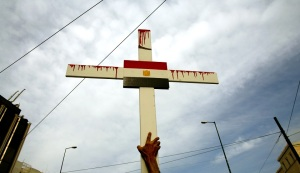 Egyptian Coptic Christian holds cross during a demonstration outside Egyptian embassy in Athens