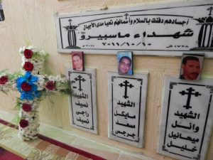 The plaque reads: The Martyrs of Maspero, with a date of October 10, 2011. One relative explained it is the 10th because that is when the autopsies were finalized, though the massacre took place on the 9th. The phrase above says: Their bodies are buried in peace, and their names live throughout the generations.