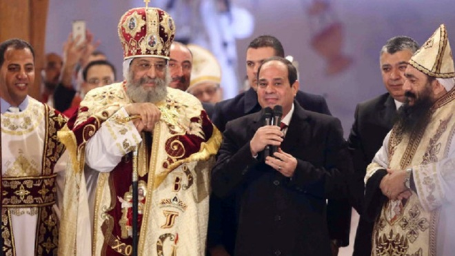 Egyptian President Sisi talks next to Coptic Pope Tawadros II as he attends Christmas Eve Mass at St. Mark's Cathedral in Cairo