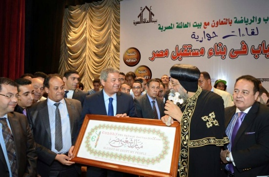 Pope Tawadros presenting Minister of Youth Khalid Abdel Aziz with a commemorative gift, quoting Isaiah 19:25 in Coptic, Arabic, and English.