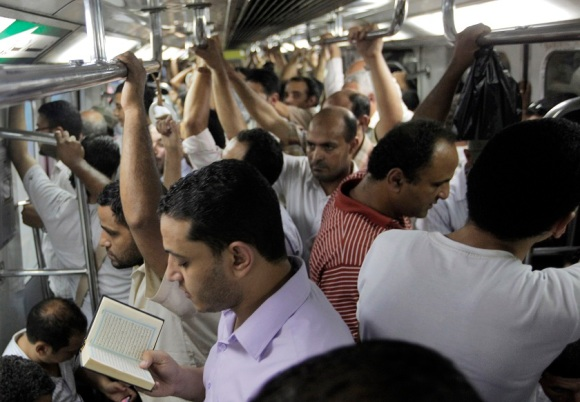 An Egyptian man reads the Quran while riding the metro (AP Photo/Amr Nabil)